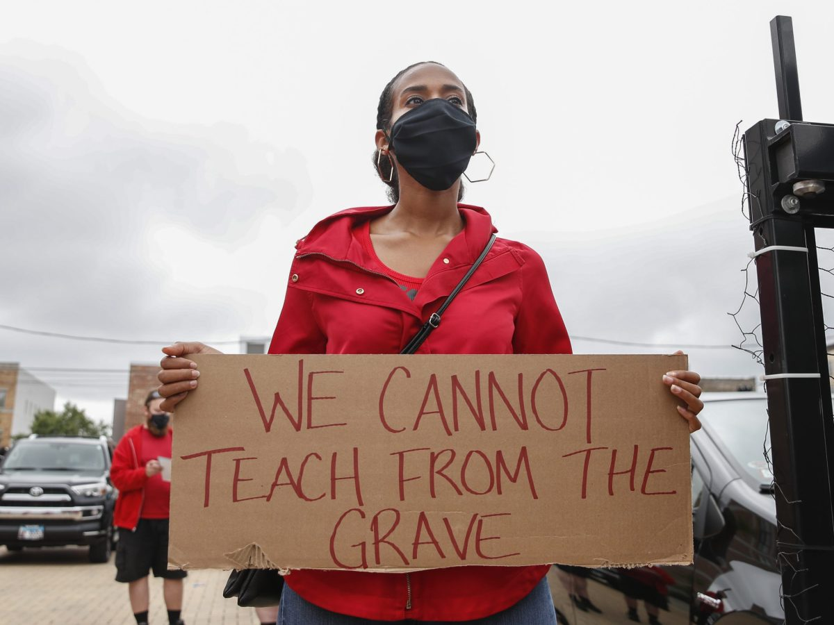 """A teacher at a Chicago Teachers Union protest holds a sign reading """"We cannot teach from the grave."""""""