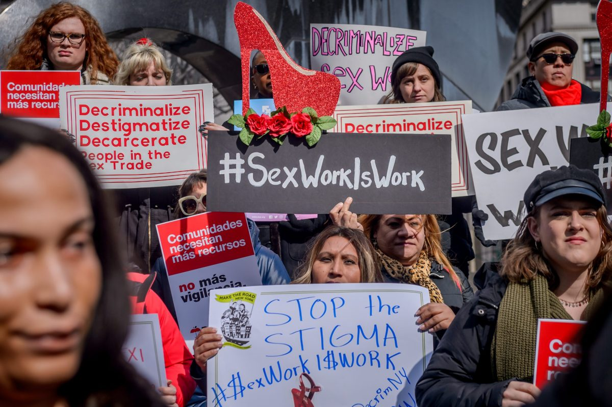 People holding signs reading #SexWorkIsWork