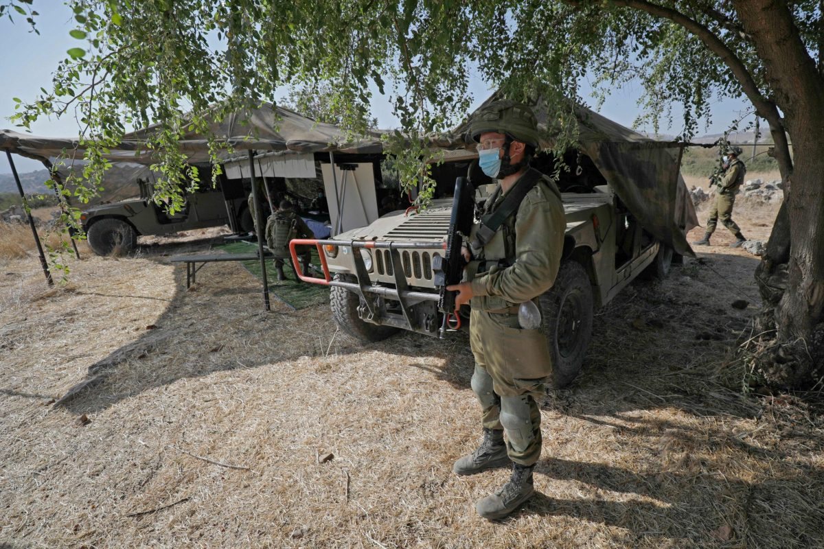 "An Israeli soldier, mask-clad due to the COVID-19 coronavirus pandemic, stands guard next to an outpost and army humvees during the ""Deadly Arrow"" military drill near Kibbutz Ravid in the northern part of Israel."