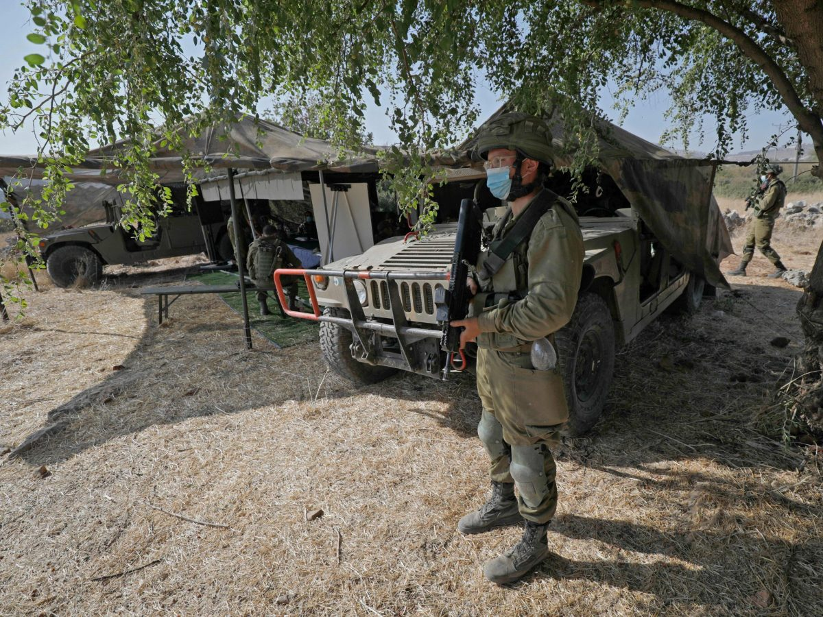 """An Israeli soldier, mask-clad due to the COVID-19 coronavirus pandemic, stands guard next to an outpost and army humvees during the """"Deadly Arrow"""" military drill near Kibbutz Ravid in the northern part of Israel."""