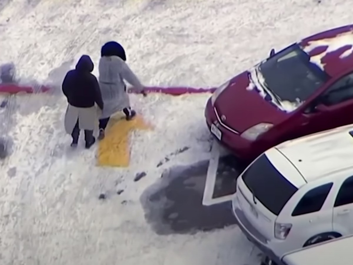 Two people walking carefully through an icy parking lot