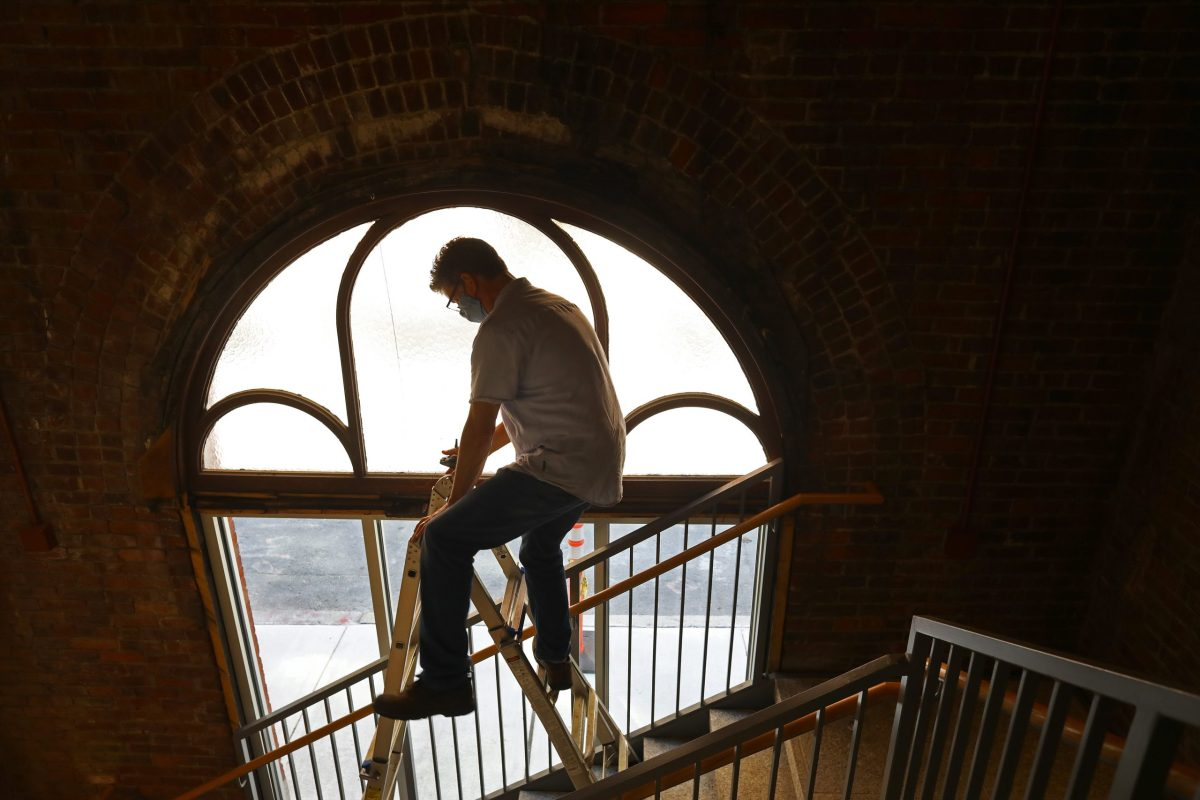 Don Garvin, the project manager for the renovation at Saint Cecilia Parish in Boston, balances on this ladder to take a measurement of the decorative arched window