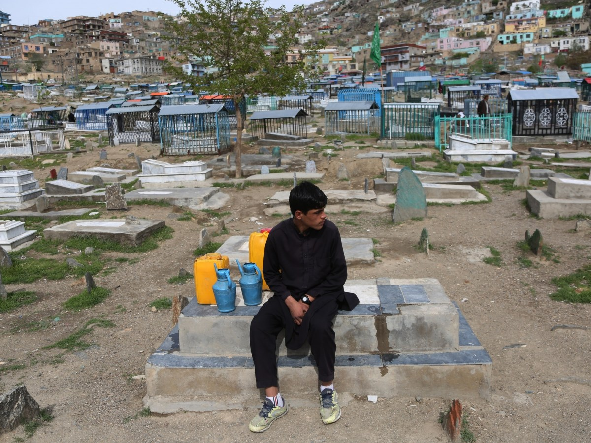 An Afghan boy sells water at a graveyard in Kabul