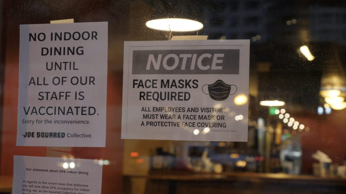 Signs indicating that indoor dining is closed and face masks are required