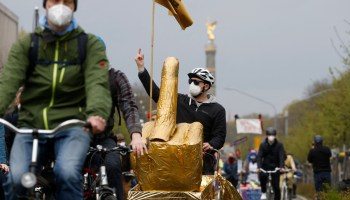 A Berlin protester with a golden middle finger attached to his bicycle