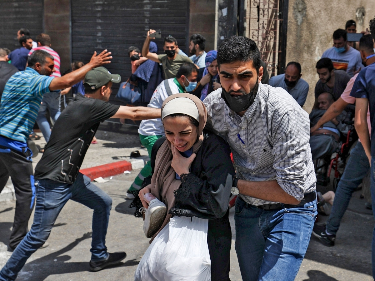 Palestinians evacuate a building targeted by Israeli bombardment