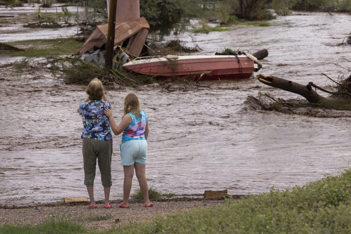In Roosevelt, Arizona, two residents look at possessions washed away by a flash flood