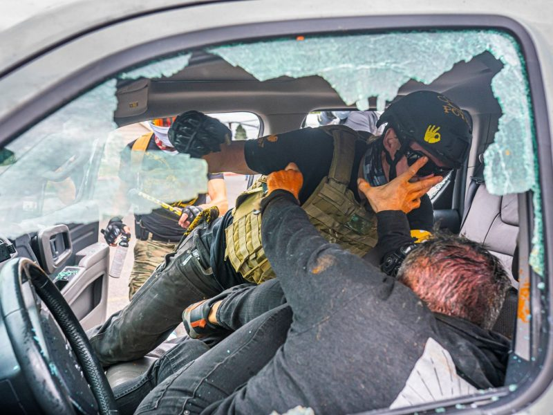 A member of the far-right group Proud Boys and a left-wing counter protester fight in a truck on August 22, 2021 in Portland, Oregon