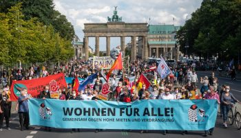 """Participants in a rally against high rent in Berlin hold a banner with the inscription """"Wohnen für Alle!"""" (Housing for All)"""