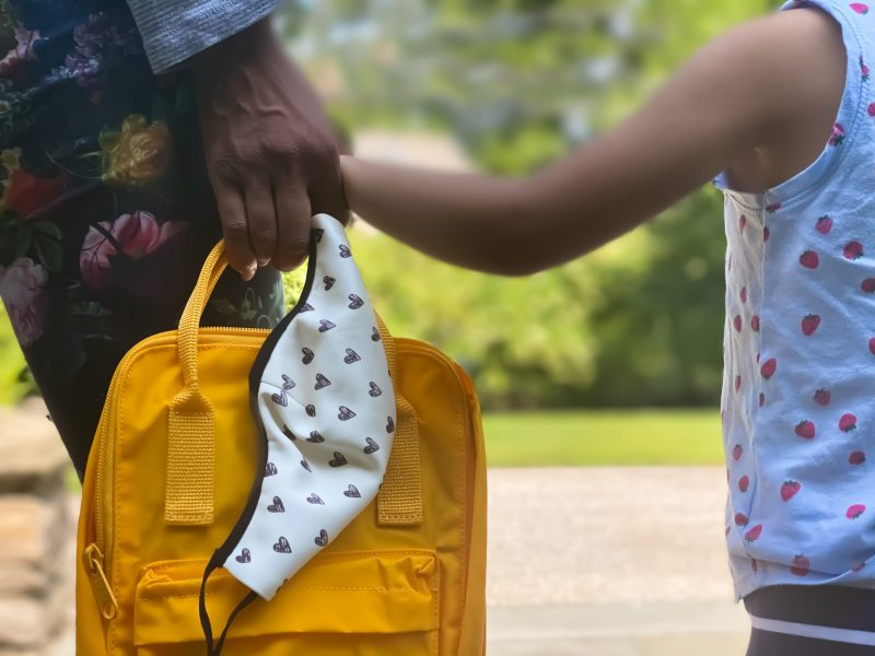A mother and child waiting together for a school bus