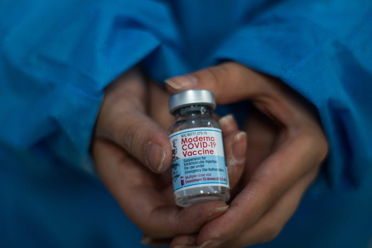 A nurse shows the vial of the Moderna novel Coronavirus vaccine