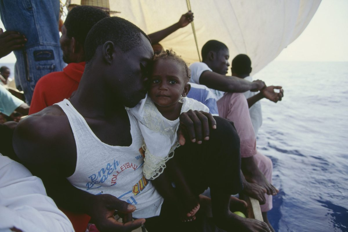 A man holds his child on board a Haitian Refugee boat heading across the Atlantic Ocean to the United States