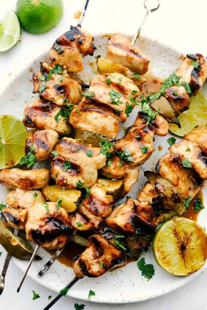 Grilled Key Lime Chicken on skewers on a white plate with fresh cut lemon on the side.