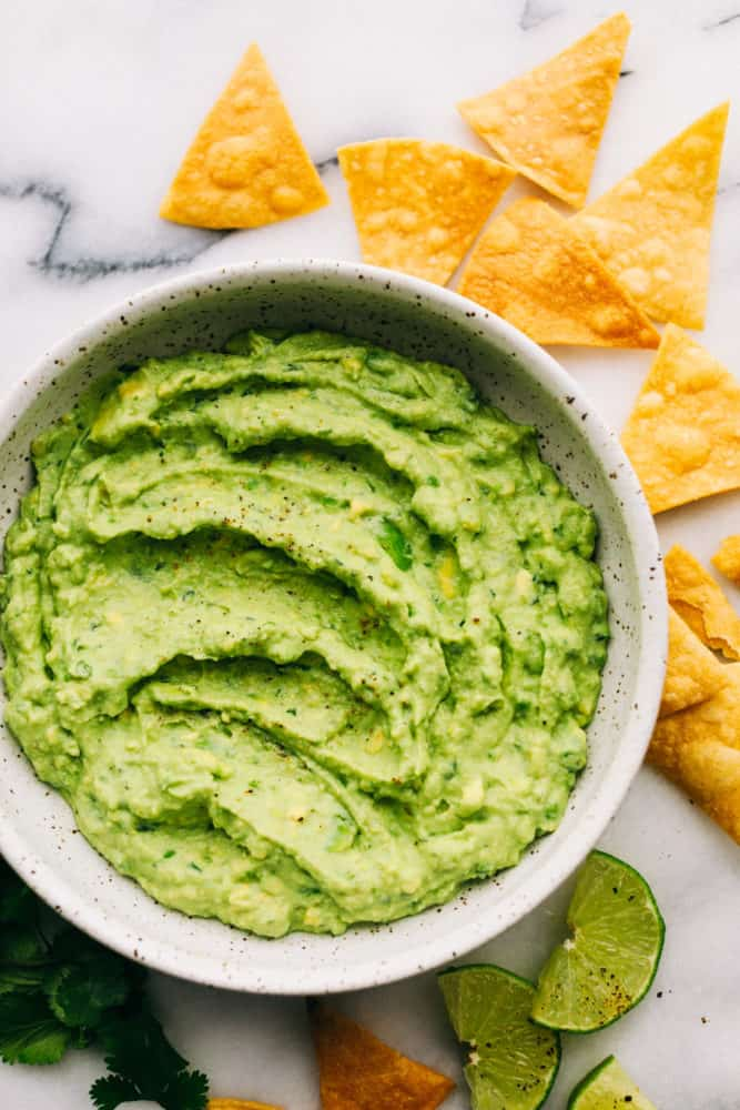 creamy avocado dip in a bowl with chips and lime slices around the edges.