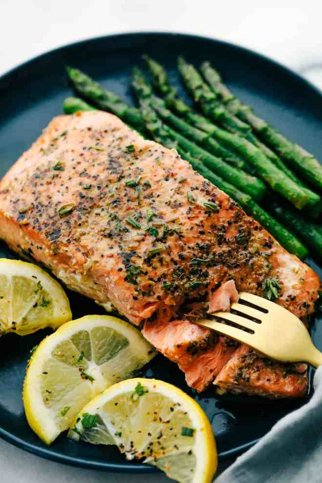 Brown butter lemon salmon on a plate with asparagus and lemon wedges.
