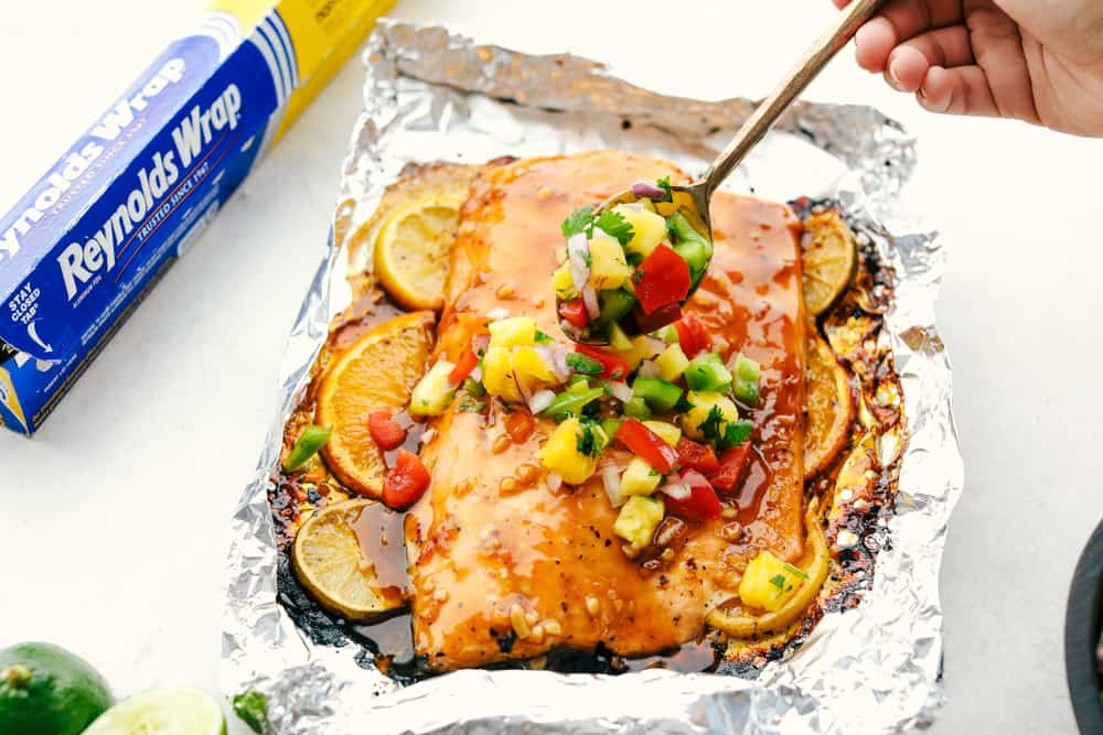 Grilled citrus salmon on Reynolds wrap aluminum foil being garnished with pineapple salsa using a silver spoon to add it to the salmon.