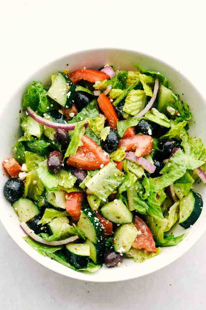Finished greek salad in a white bowl.