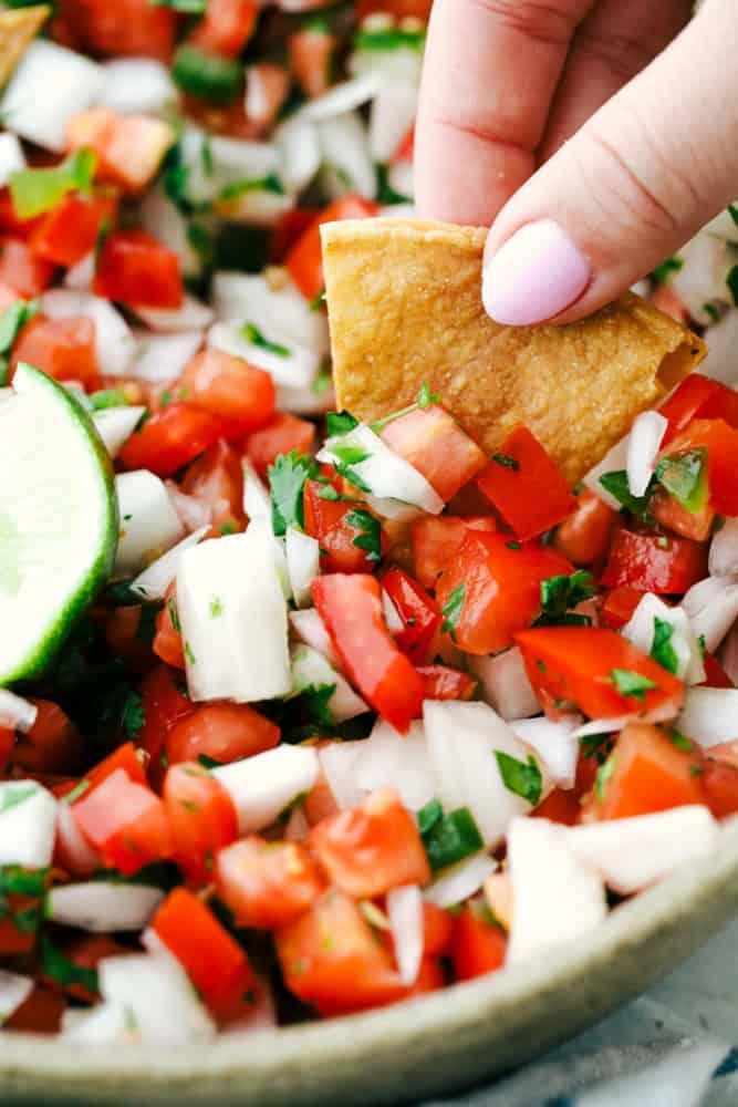 Dipping a chip into fresh pico de gallo.
