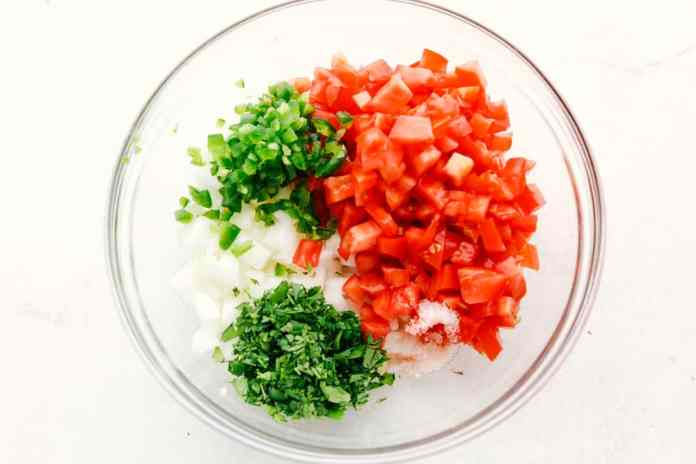 Ingredients for pico de gallo in a clear bowl.