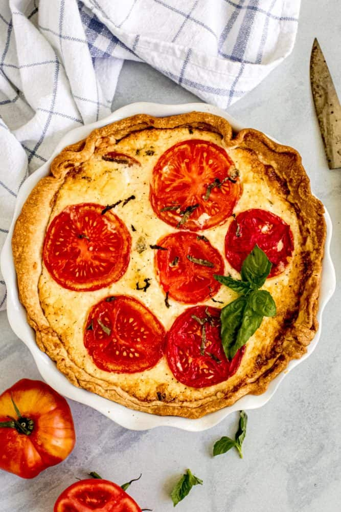Tomato pie in a white pie dish with fresh basil on top