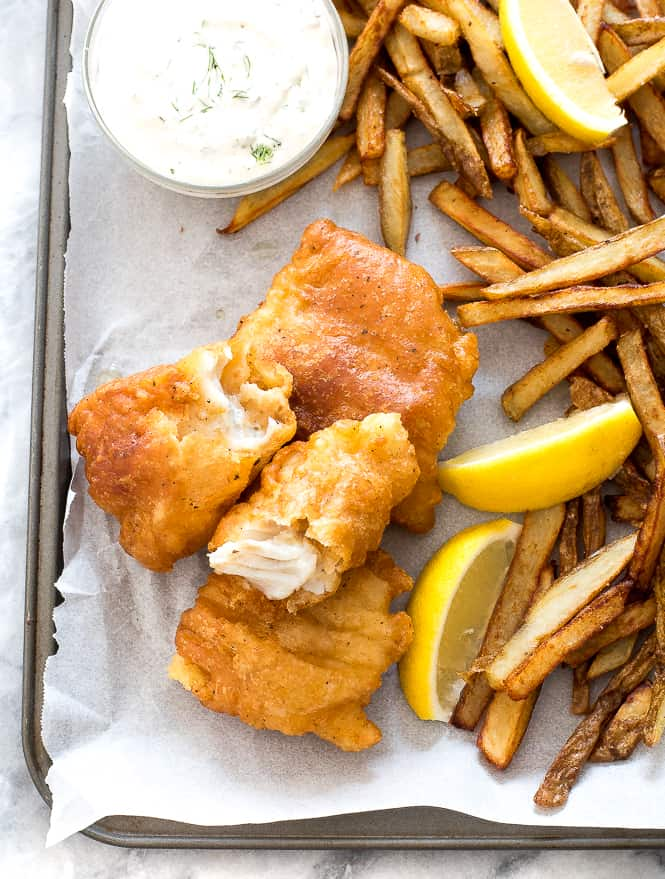 Fish on the side with French fries, coleslaw and lemon slices on the side.