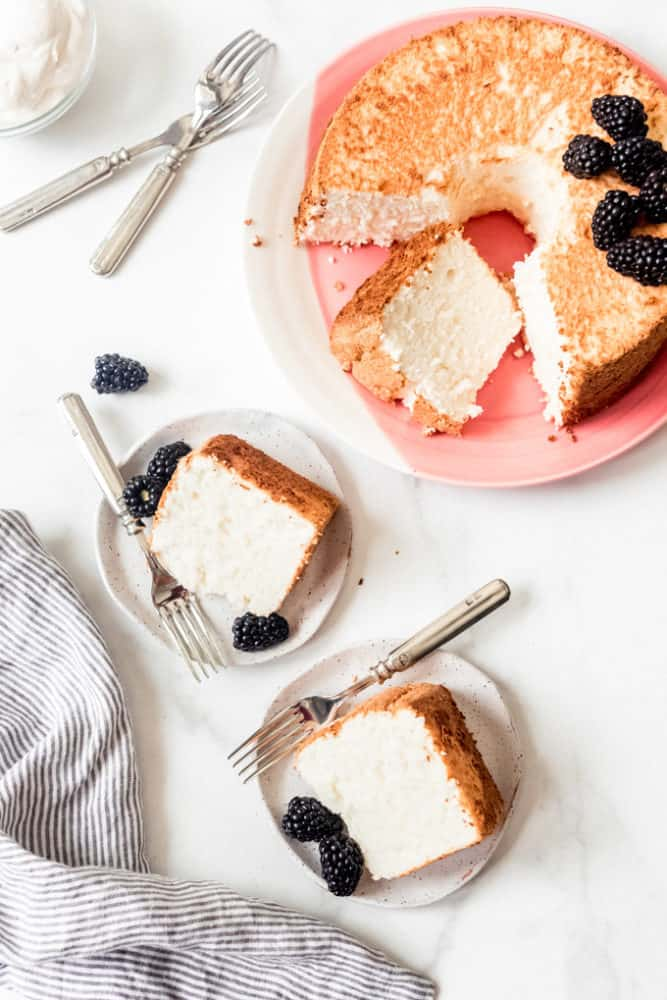 Slices of angel food cake on dessert plates with blackberries and forks next to the rest of the cake on a pink plate.