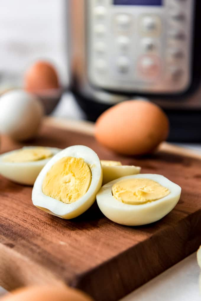 Sliced hard boiled eggs in front of an Instant Pot.