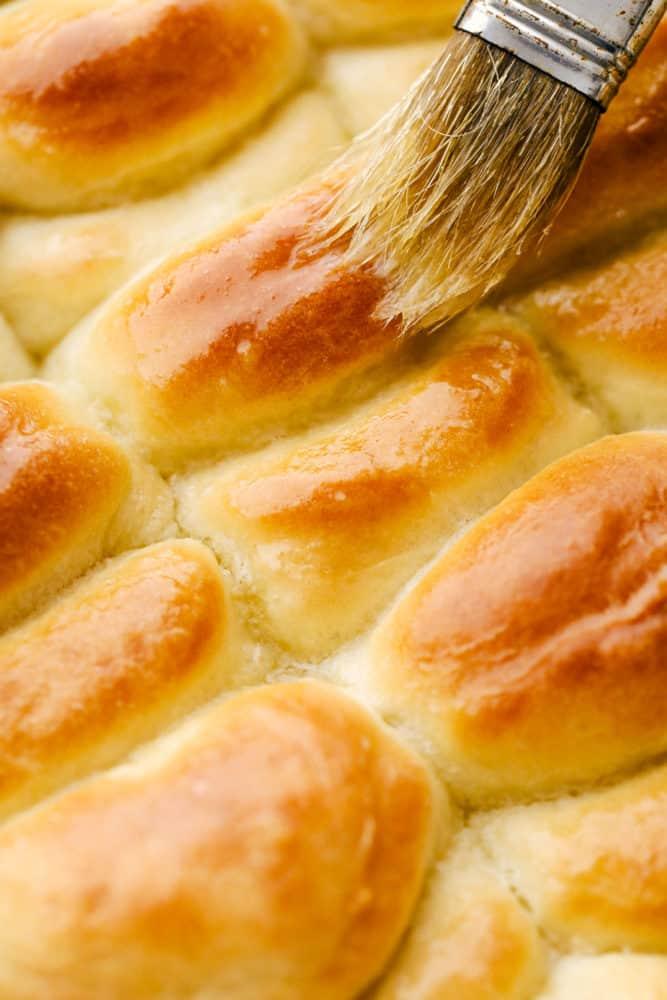 Brushing butter on golden baked Parker House Rolls