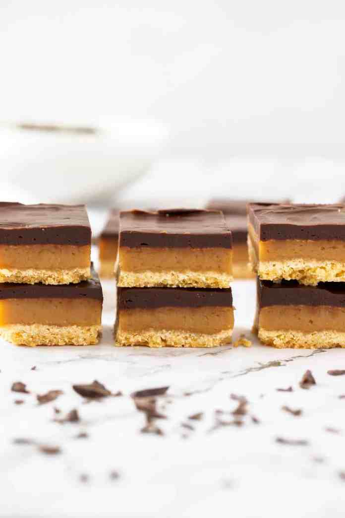 3 stacks, each with 2 pieces of millionaire shortbread. Chocolate scattered in front