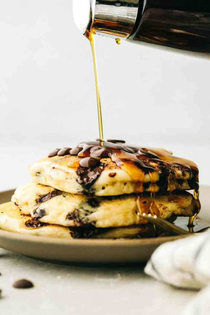 Syrup pouring on top of chocolate chip panckaes.