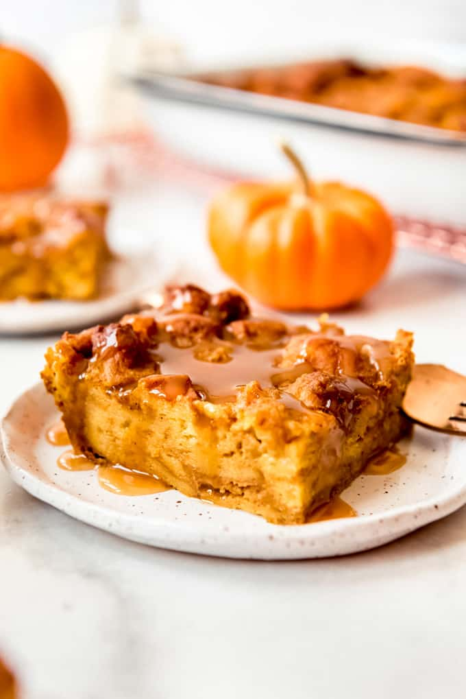 A slice of pumpkin bread pudding with caramel sauce.