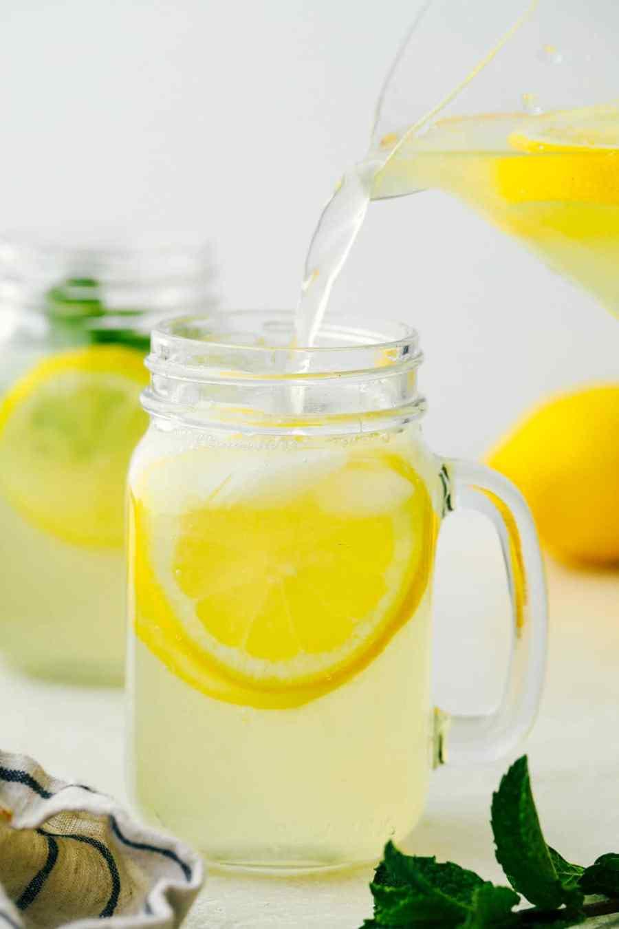 Pouring lemonade in glass mason serving jars.