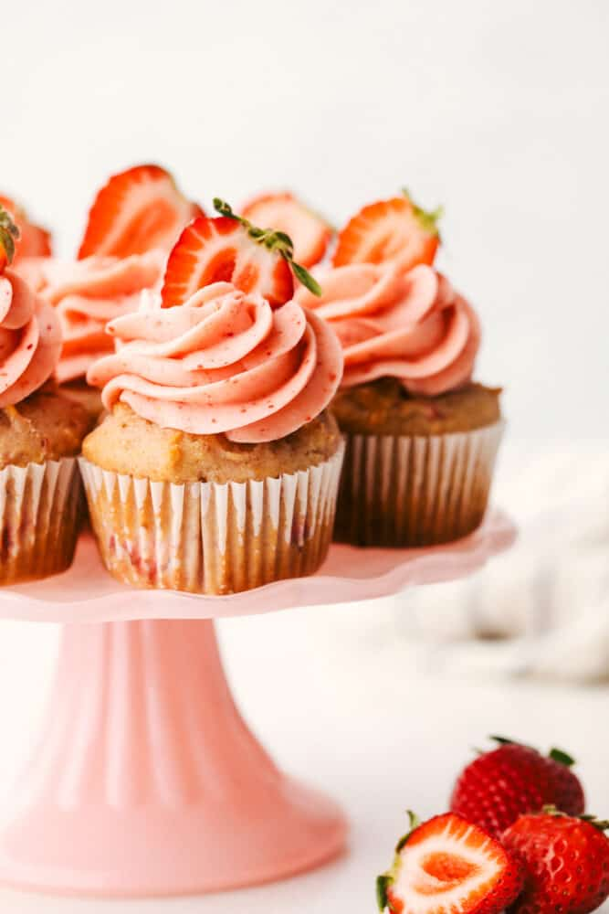 Strawberry cupcakes on a platter with frosting and strawberries on top.