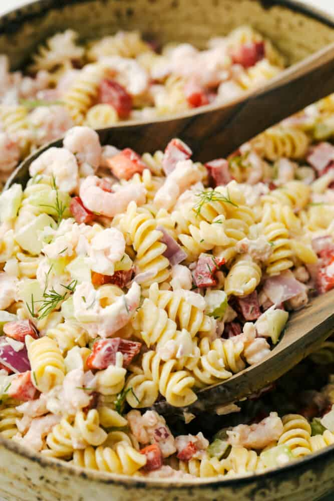 Up close photo with shrimp pasta salad and two wooden spoons in the salad.