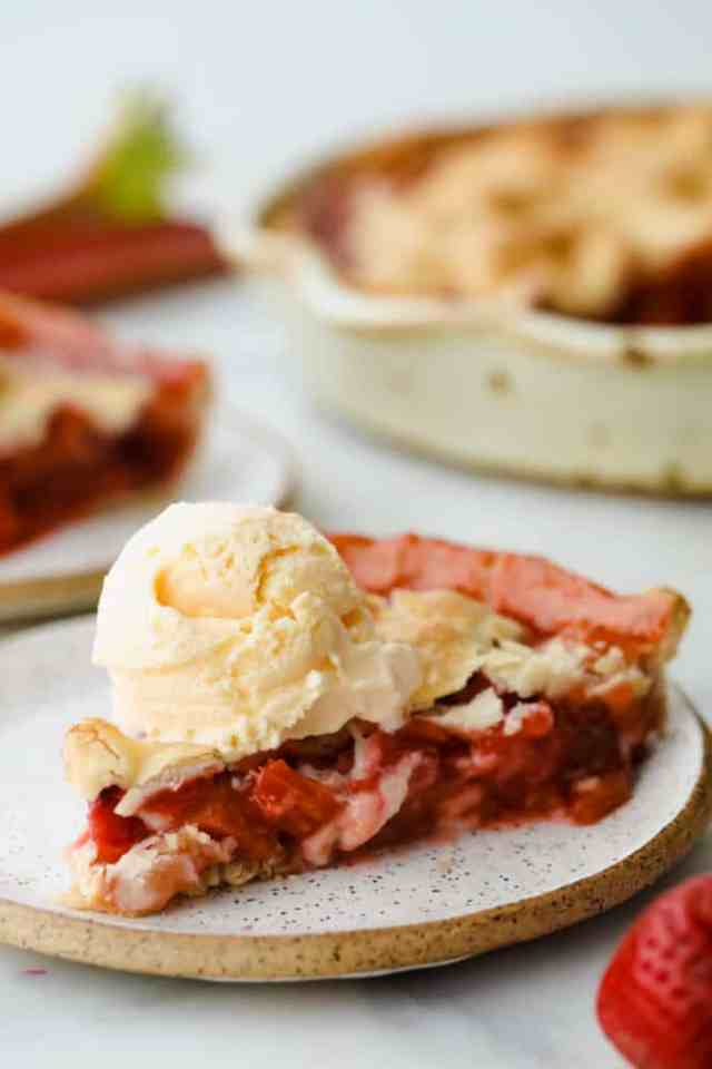 Slice of strawberry rhubarb pie with a scoop of vanilla ice cream on top