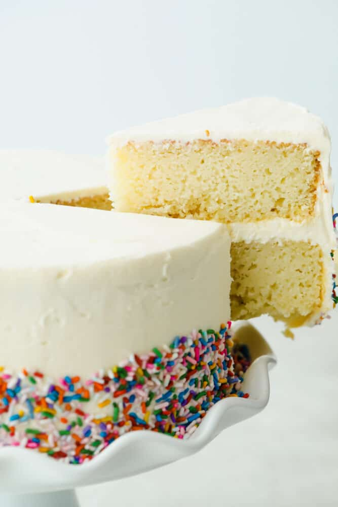 A slice of white cake cut and taken out of the cake.