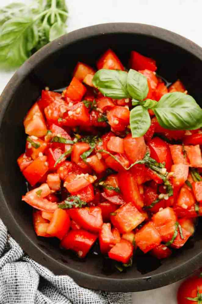 Tomato basil salad in a brown bowl.