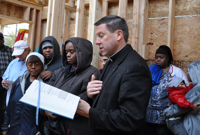 Father J. Mark Spalding, pastor of Holy Trinity Church, said the opening prayer at a Habitat for Humanity house blessing Oct. 19, 2013. Holy Trinity and St. Matthews Episcopal churches came together to build a house for Emma Eddins, at left with white hat and wearing glasses. The home is located in the Russell neighborhood. (Record File Photo by Jessica Able)