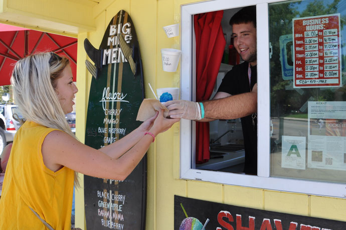 Mike Buchanan handed Allie Meyer, left, a shaved ice July 31. The teen owns and operates Big Mike's Shaved Ice,  located at 1351 Bardstown Road.