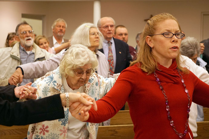 Parishioners at St. Pius X Church prayed the Our Father at the parish's closing liturgy Nov. 21. St. Pius and St. Barnabas Church will merge to form St. John Paul II Church effective Nov. 29