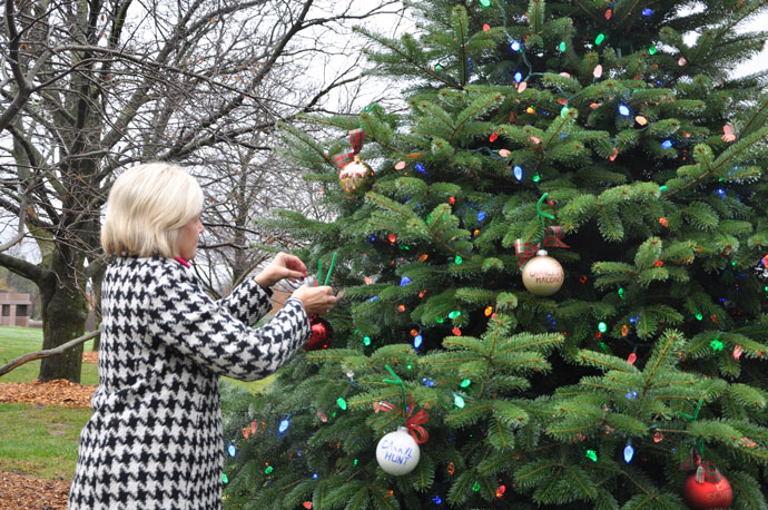 "Julie Borders, a family counselor at Catholic Cemeteries, placed an ornament on the ""tree of remembrance"" at Calvary Cemetery, 1600 Newburg Road, Dec. 1. (Record Photos by Jessica Able)"