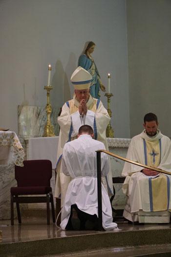 Archbishop Joseph E. Kurtz prayed over Deacon Sanders, below, during the diaconate ordination.