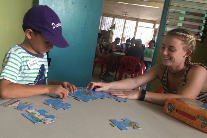 Sacred Heart Academy junior Emma Greenwood played with a little boy at the Hand in Hand Ministries Children's Center in Managua, Nicaragua. A dozen SHA students traveled to Managua to build a house during spring break. (Photo Special to The Record)