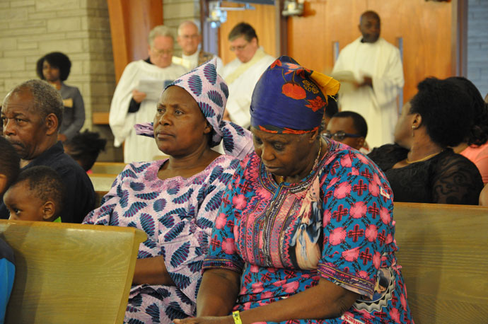 Nyirabahire Cesaree, left, and Mukarugabira Laurence, sat in silence prior to the start of the Memorial Service for the Victims of Violence, War and Genocide in Africa April 16 at St. Thomas More Church