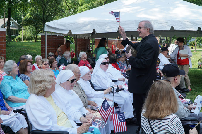 Father William Hammer, pastor of St. Margaret Mary Church, greeted Little Sisters of the Poor at a Flag Day celebration June 14. Father Hammer delivered the invocation and led prayer.