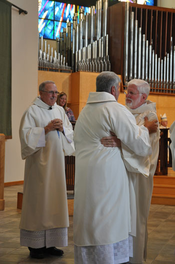 Deacon Pat Wright, at right, the former director of the Diaconate Office, embraced the newly-ordained Deacon Stephen A. Age. Deacon Denny Nash, who became the new director of the Diaconate Office in May, looked on.