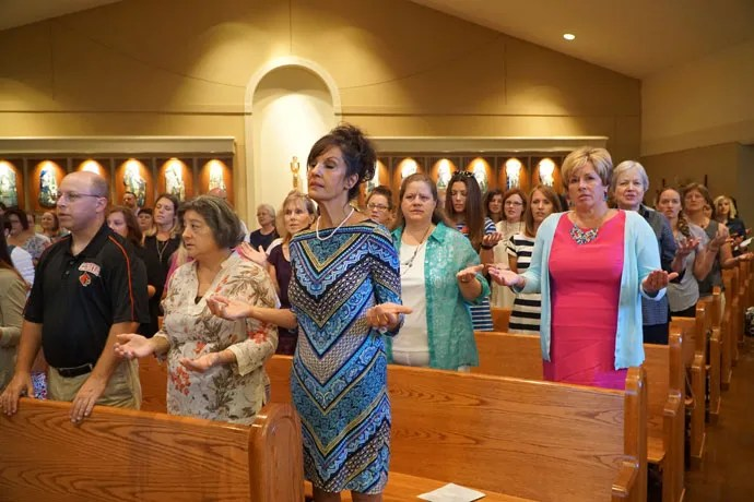 "Teachers pray the ""Our Father"" at the annual liturgy held prior to the start of the school year, held this year at St. Lawrence Church."