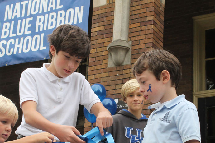 St. Francis of Assisi School students, from left, Todd Nieman, Ben Kenney, Woody Schoenbachler and Elliott Leib, tied blue ribbon on the railing of the school entrance in September. The Highlands school was named a 2016 National Blue Ribbon School by the U.S. Department of Education. (Photo Special to The Record)