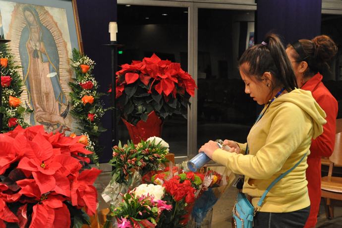 Stivalys Martinez lights a candle to place near an image of Our Lady of Guadalupe Dec. 12 at a Mañanitas prior to the 5 a.m. Mass at Epiphany Church, 914 Old Harrods Creek Road. The U.S. bishops asked that the Dec. 12 feast of Our Lady of Guadalupe be a day of prayer with a focus on migrants and refugees. Our Lady of Guadalupe is the patroness of the Americas. (Record Photo by Jessica Able)