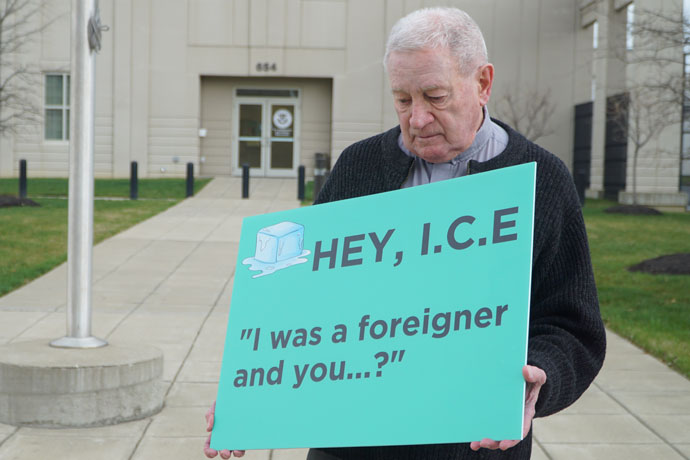 Father James Flynn, a retired priest of the Archdiocese of Louisville who is active in Hispanic and Latino ministry, kept vigil on a rainy Monday, March 27, outside the Immigration and Customs Enforcement office in downtown Louisville. The 87-year-old stands with a green sign — that alludes to Chapter 25 in the Gospel of Matthew — several days each week, saying hello to people who happen by and prayerfully supporting people who have been detained inside. (Record Photo by Marnie McAllister)